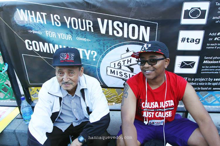 Don Cande and Robbie Clark from Causa Justa :: Just Cause and the Plaza 16 Coalition, sitting in front of the banner for senseofplace LAB's project: What is your Vision for your Community? Photo by Hanna Quevedo.